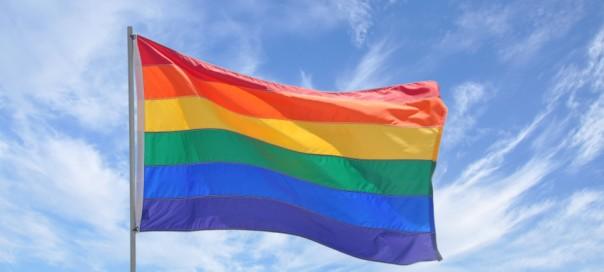 Gay Pride Flag Pole Waving in Blue Cloudscape Sky